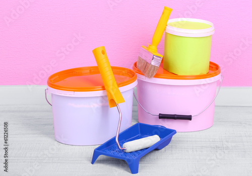 Paints, roll and paintbrush on floor in room on wall background