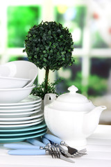 Clean dishes on table on window background