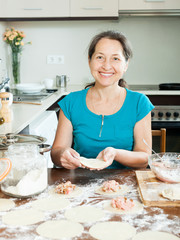 Mature woman making meat dumplings