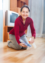 mature housewife polishing parquet floor