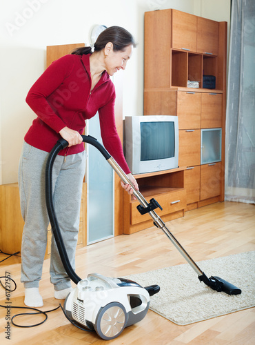 mature woman cleaning with vacuum cleaner