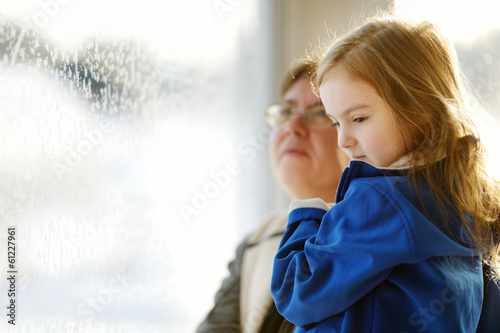 Little girl and grandma staring through a window