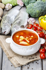 Bowl of tomato soup on wooden table