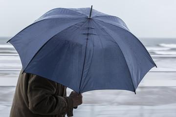 Hombre con paraguas azul