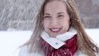 Young woman blows snow at camera.