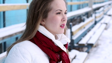 Young wooman cheering at an empty stadium in winter. Air kiss.