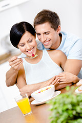 Man feeds and hugs his girlfriend sitting at the kitchen