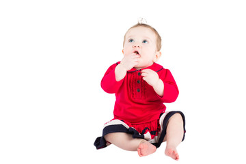 Cute baby girl in a red dress, isolated on white