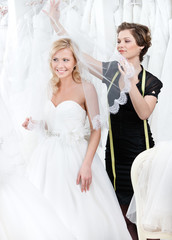 Shop assistant puts wedding veil on the head of the bride