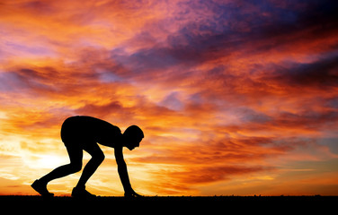 Silhouette of athlete in position to run on sunset background