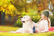 Female lying on grass with her dog in a park