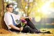 Handsome guy with a bunch of flowers in park relaxing