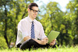 Young businessman with glasses sitting on grass and working
