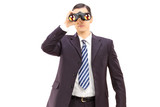 Male businessman watching through binoculars