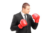 Young businessperson in suit with red boxing gloves posing