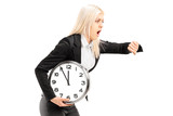 Young businesswoman running late with a wall clock in her hand