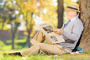 Senior gentleman seated on a grass reading newspaper in a park