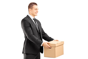 Smiling businessman in suit giving a box to someone
