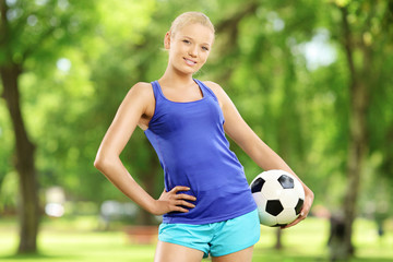 Young active female holding a ball in park