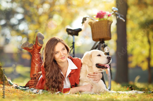 Beautiful female lying on a green grass with dog in a park