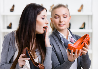 Salesperson offers stylish pumps for the female customer