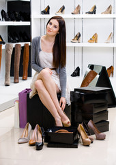 Woman sitting on the chair and trying on shoes
