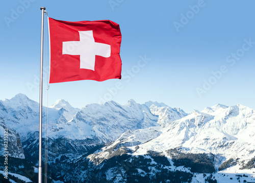 Leinwanddruck Bild Swiss Flag Flying Over Alpine Scenery