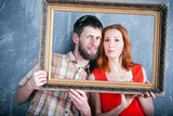 Portrait of young loving couple looking through photo frame