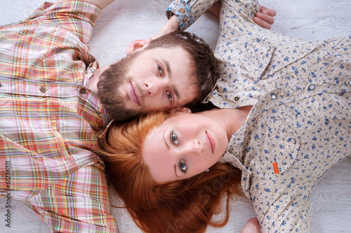 Young beautiful couple lying on the floor and looking up