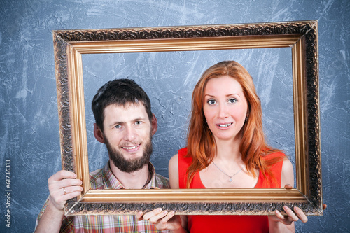 Portrait of young loving couple looking through picture frame
