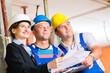 Team auf Baustelle kontrolliert Bau Pläne