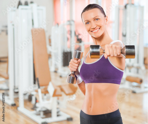 beautiful feamale exercising with weights in gym