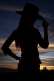 silhouette of cowgirl tipping her hat at sunset