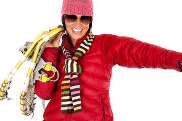 Smiling woman in winter wear carrying snow shoes