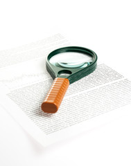 Magnifying glass lies on a piece of paper