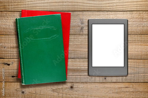 Ereader and books on wooden background
