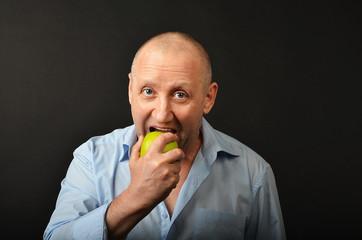 Мужчина откусывает яблоко.