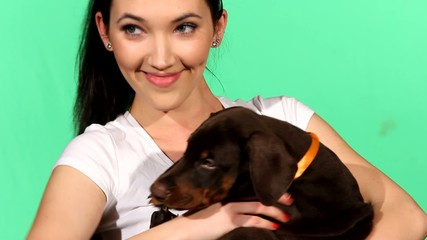 Brunette girl with her doberman puppy isolated