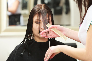 Hairstylist cutting hair woman client in hairdressing salon