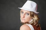 Young blonde woman with serious face wearing white hat
