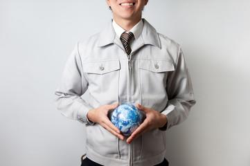地球儀を持つ作業服の男性
