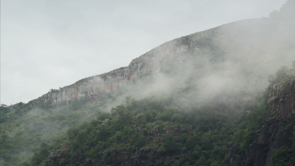 Timelapse of mist flowing over a pair of steep hills.