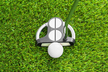 Close up of golf ball and putter on green