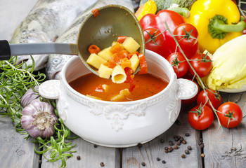 Bowl of tomato soup on wooden table among variety of vegetables