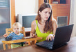 serious mother with baby using laptop