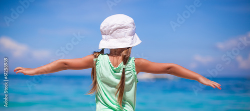 Little happy girl on a tropical beach with turquoise water