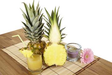 Halbierte Ananas und ein Glas Ananassaft auf einem Strohset