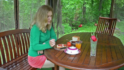 blond woman eat sandwich and drink juice in garden summer house
