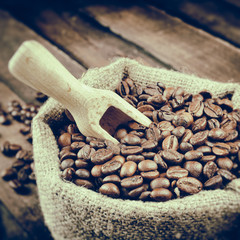 Vintage stylized photo of sack with coffee beans and wooden scoo