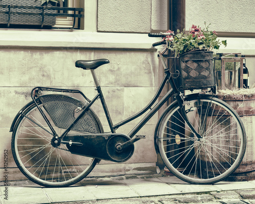 Fotobehang Fiets Vintage stylized photo of Old bicycle carrying flowers